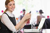 Happy businesswoman sending a text