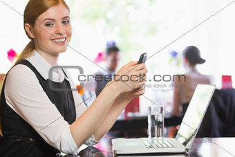 Happy businesswoman sending a text