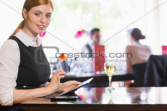 Businesswoman using tablet and looking at camera