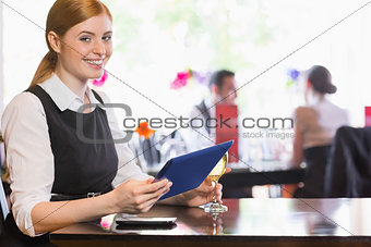 Smiling woman using tablet while holding wine glass and looking at camera