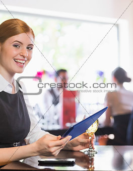 Happy businesswoman holding tablet and wine glass looking at camera