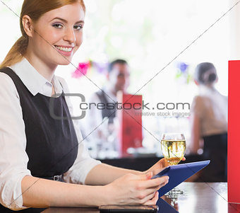 Attractive businesswoman holding tablet and wine glass and smiling at camera