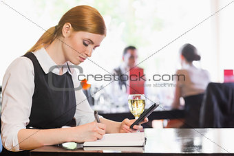 Concentrated businesswoman holding phone while writing