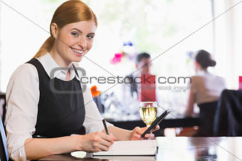 Smiling businesswoman holding phone and writing while looking at camera