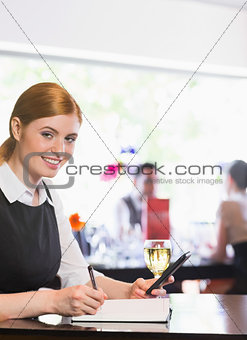 Smiling businesswoman writing and holding phone while looking at camera