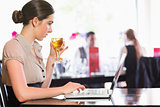 Attractive businesswoman holding wine glass while working on laptop