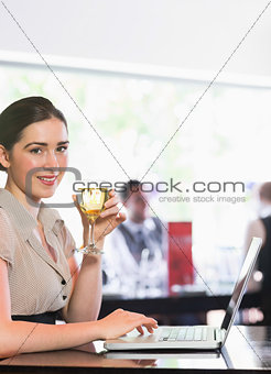 Smiling businesswoman using laptop while holding wine glass