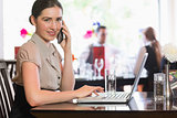 Businesswoman calling on phone using laptop