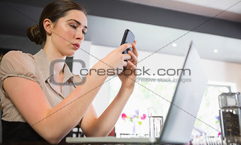 Concentrated businesswoman texting on phone