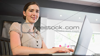 Smiling businesswoman typing on her laptop while looking at camera
