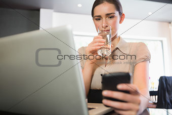Businesswoman using phone in a cafe