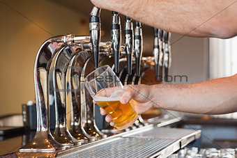 Mans hand pouring beer