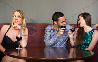 Blonde woman feeling lonely as two people are flirting beside her