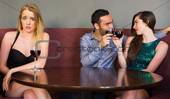 Blonde woman feeling jealous as two people are flirting beside her