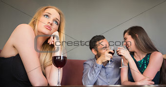 Blonde woman feeling jealous of two people are flirting beside her