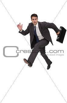 Focused businessman holding a briefcase and running
