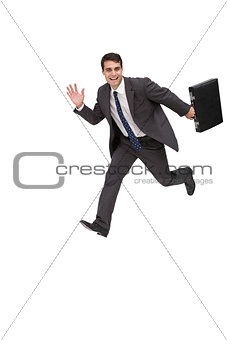 Happy businessman holding a briefcase and running
