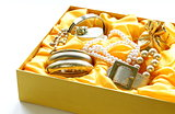 gold jewelry and pearls in a yellow gift box