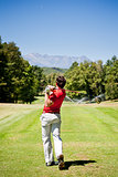 Golf player performs a tee shot