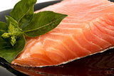 The plate with appetizing salmon and the sprig of basil