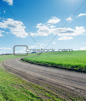 winding rural road under blue cloudy sky