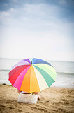 Woman sat on the beach with umbrella