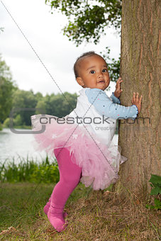 African little girl is holding the tree