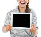 Closeup on smiling young woman showing tablet pc blank screen