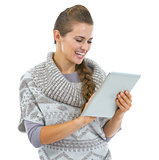 Happy young woman in sweater and christmas hat using tablet pc