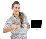 Smiling young woman in sweater and christmas hat with tablet pc