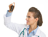 Doctor woman looking on medicine bottle