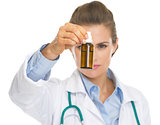 Closeup on medicine bottle in hand of doctor woman