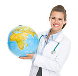 Smiling doctor woman holding earth globe