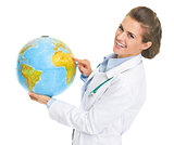Smiling doctor woman pointing in earth globe