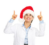 Smiling doctor woman in santa hat pointing up on copy space