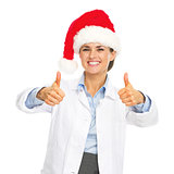 Smiling doctor woman in santa hat showing thumbs up