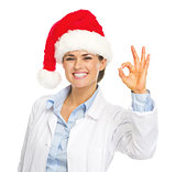 Happy doctor woman in santa hat showing ok gesture