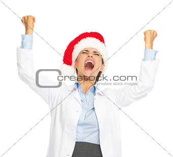 Happy doctor woman in santa hat rejoicing success