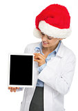 Happy doctor woman in santa hat showing tablet pc blank screen