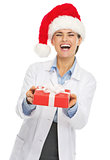 Happy doctor woman in santa hat giving christmas present box