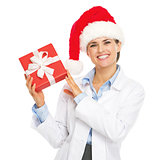 Happy doctor woman in santa hat showing christmas present box