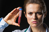 Doctor woman showing test tube isolated on black