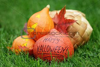 three Halloween pumpkins on green grass