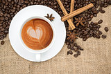 Cup of coffee with heart shape in foam on hessian background