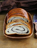 Biscuit roll with poppy seeds on a wooden plate