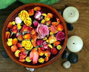 wooden bowl with roses and petals of flowers - spa concept