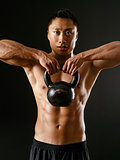 Asian man exercising with kettlebell