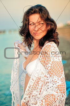 Happy girl in a white shawl on the beach.
