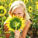 Young blonde girl playing with sunflower
