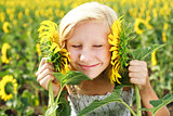 Young girl in the field playing with sunflowers
